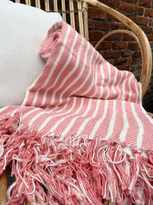 "This medium weight, coral striped blanket, by Carol & Frank, measures 50"" x 60"" and is 100% cotton. The stripes create a herringbone pattern and end with tassels at each end."