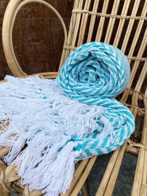 "This medium weight, aqua, herringbone blanket, by Carol & Frank, measures 50"" x 60"" and is 100% cotton. The stripes create a herringbone pattern and end with tassels at each end."