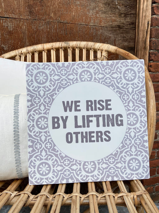 "Gray and White metal sign reads, ""WE RISE BY LIFTING OTHERS"". Hangers are attached to the back so it is ready to hang. Measures 12"" square."