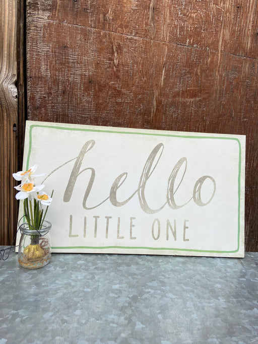 "Cream, grey, and green wooden sign that reads, ""hello LITTLE ONE"". This sign measures approx. 10"" x 18"" and come equipped with hardware on the back for easy installation."