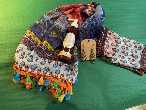 Bring a bit of energy into someone's life with this lightweight boho scarf with tassels. We will add in a pair of matching wooden earrings and some warm honey body lotion. Just the thing for making a splash when you go out, or bring a little cheer to yourself while staying in.