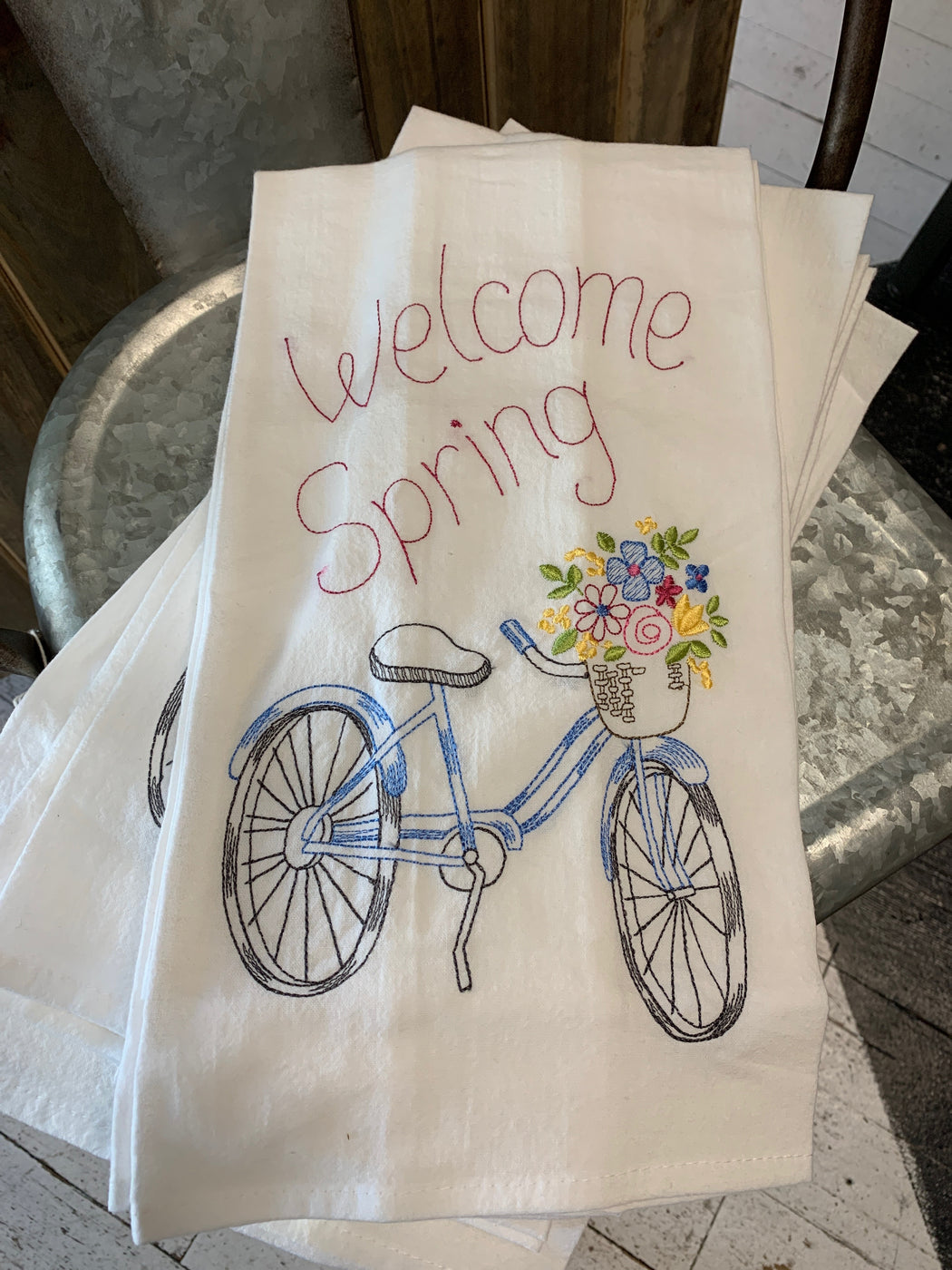 "This fun, embroidered towel has a bicycle with fresh flowers and reads, ""Welcome Spring""."