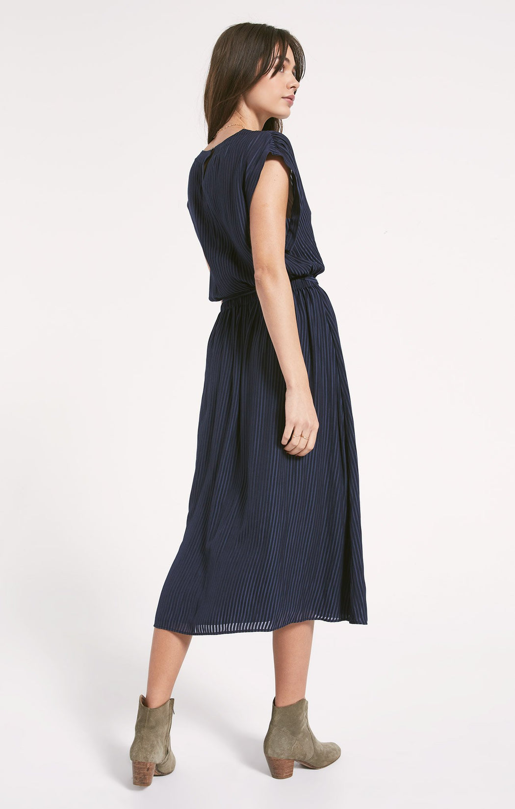 This flowy, relaxed surplice midi dress is made from a soft and lightweight polyester knit fabric. The Chalet Dress features a faux wrap top with a v-neck design and keyhole style button closure at the back. The full skirt has shirring along the elastic waistband, with a belt that ties at the front. Wear this comfortable dress with boots and a statement jacket for an instant fall favorite.
