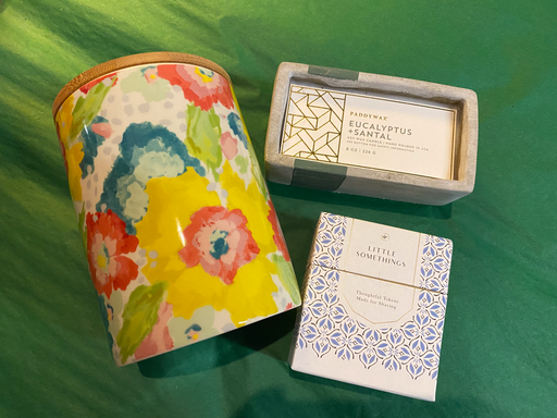 "This gift set will be sure to bring joy in abundance. The person who receives this gift will enjoy a three wick Eucalyptus + Santal candle from Paddywax, a 6"" high colorful floral print canister, and a box of ""Little Somethings""."