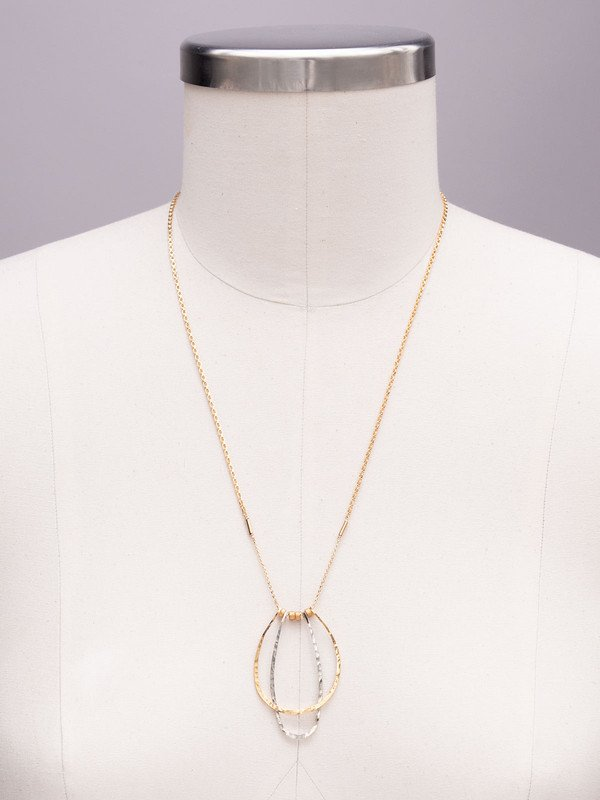 "Our In the Loop Necklace features two metallic drop ""hoops"" in modern silhouettes. Light and ultra-thin, this design makes a statement without adding any weight. Whether styled for day or night, this piece is sure to turn heads."