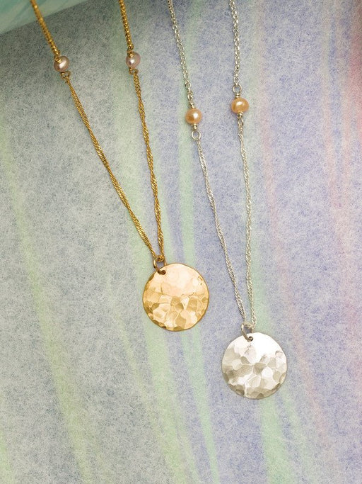 Add a touch of shimmer to your everyday look. Two styles of delicate link chain are connected by freshwater pearls and feature a single hand-hammered and formed disk pendant in this stylish, understated piece.