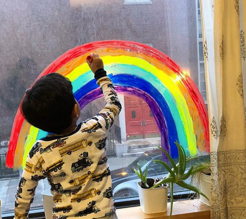boy painting rainbow on window