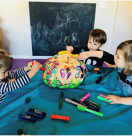 Children painting pumpkin with Kwik Stix Solid Tempera Paint