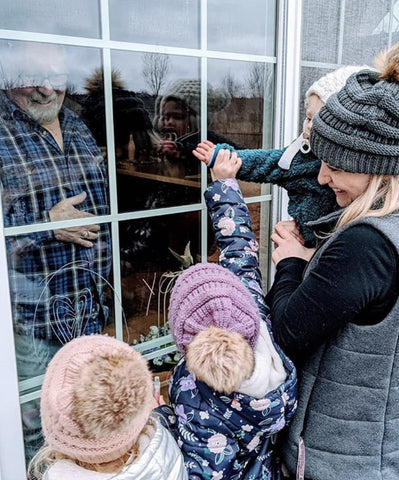 grandparents and grandchildren drawing on window