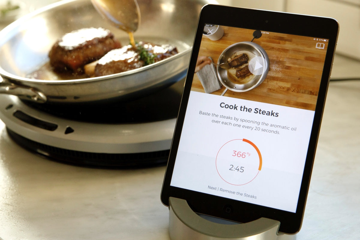 The Hestan Cue app on a tablet, with instructions on cooking a steak. In the background, a person is cooking steaks.