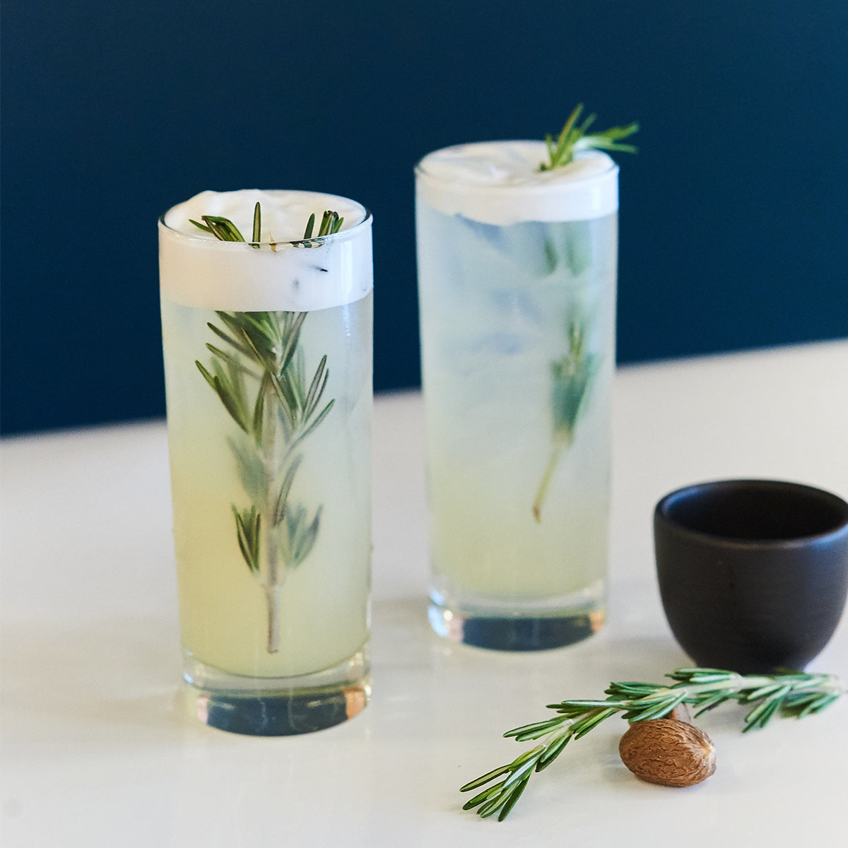 two drinks with rosemary spirgs on top