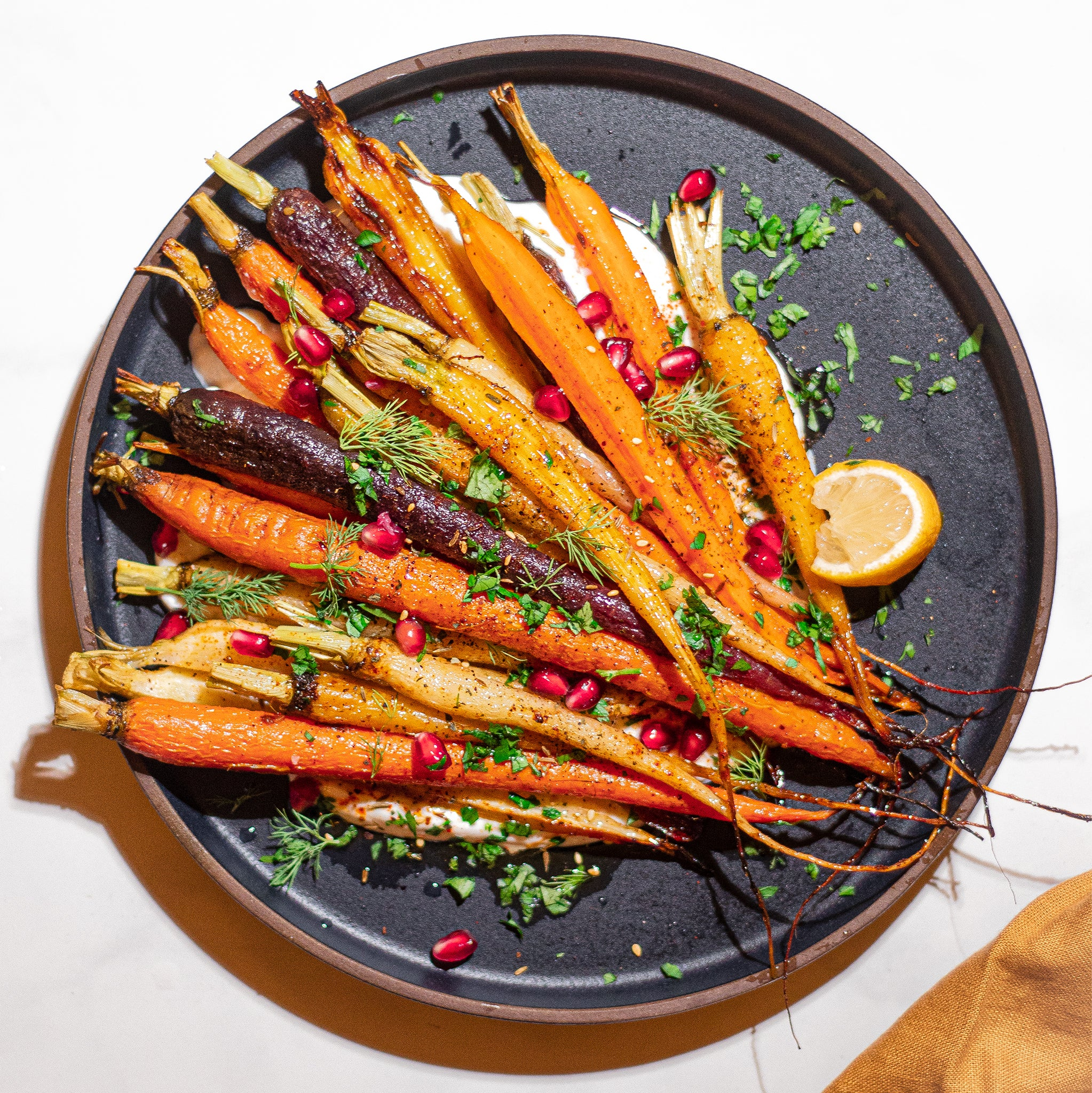 multi-colored carrots on black plate with pomegranate and honey