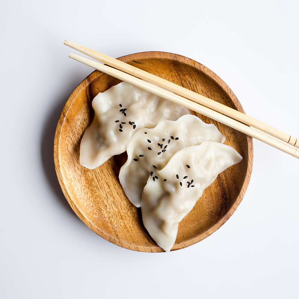 Three steamed dumplings on a wooden plate with chopsticks