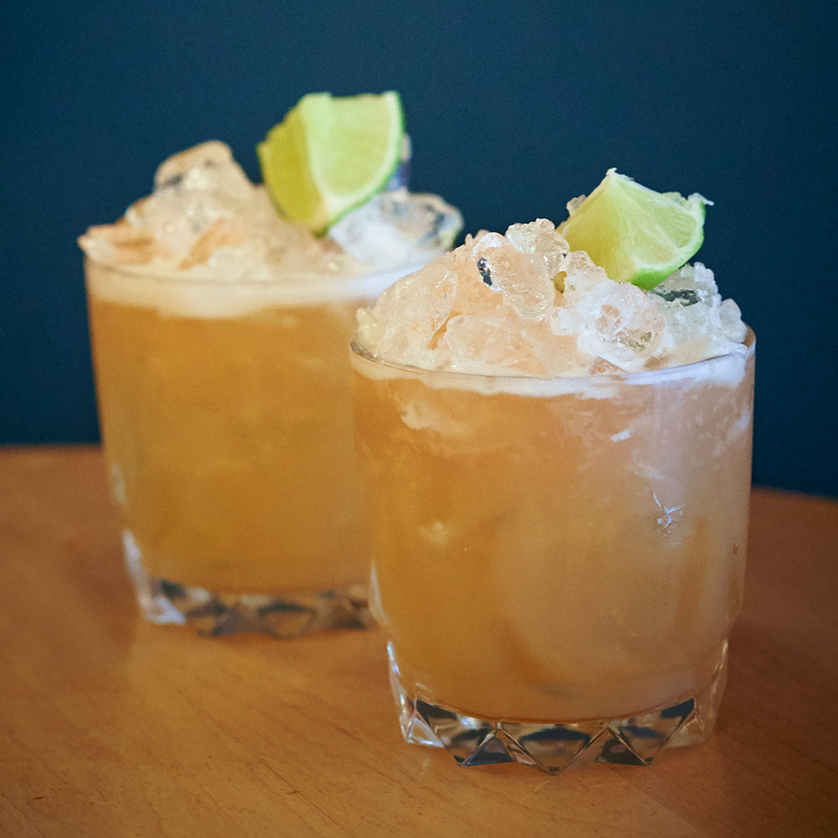two drinks topped with lime wedges