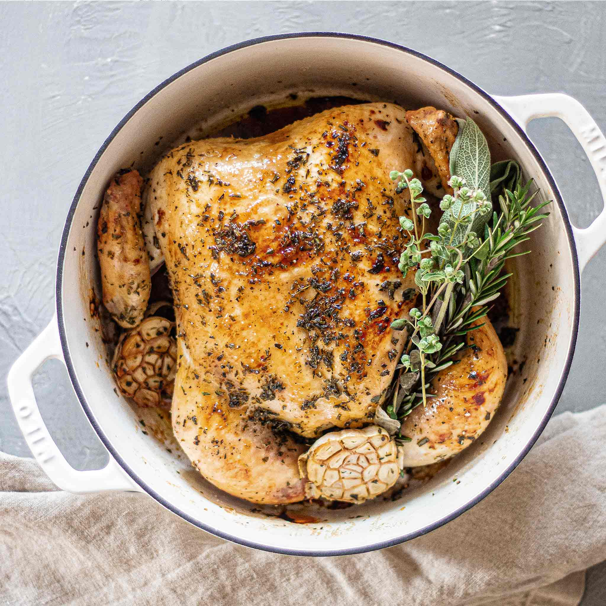 Whole roast chicken in Dutch oven with herbs, garlic and honey.