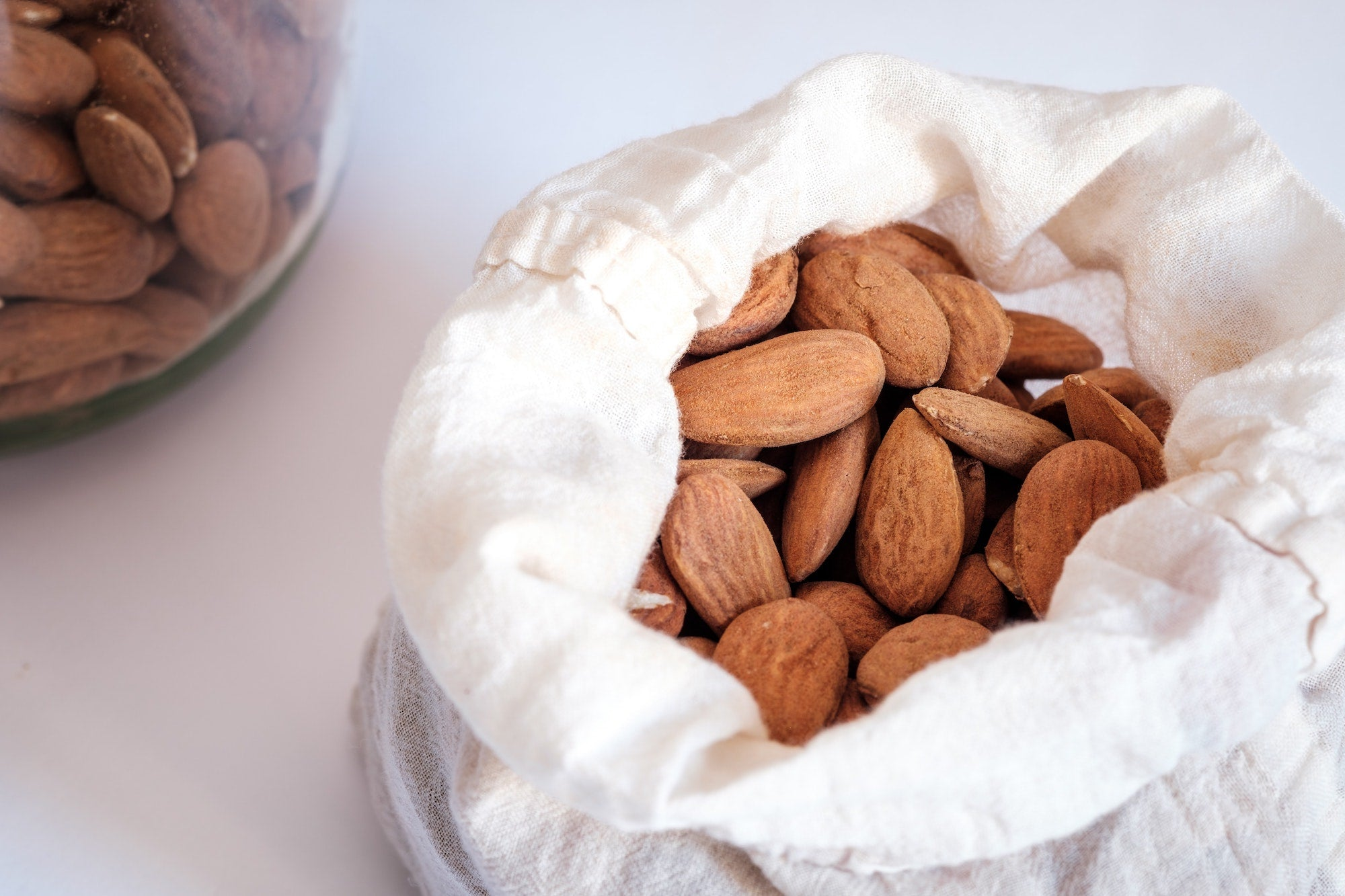A cloth bag filled with almonds rests on a table.