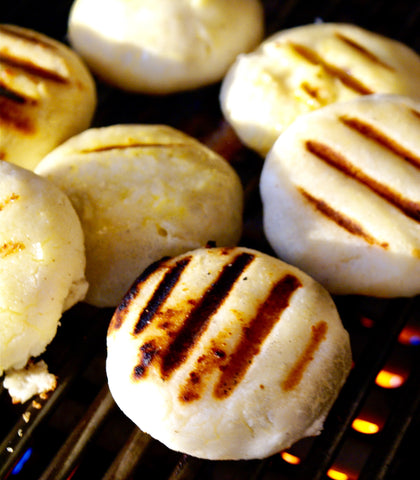 arepas cooking on a grill
