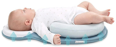 baby laying on blue infant travel bed