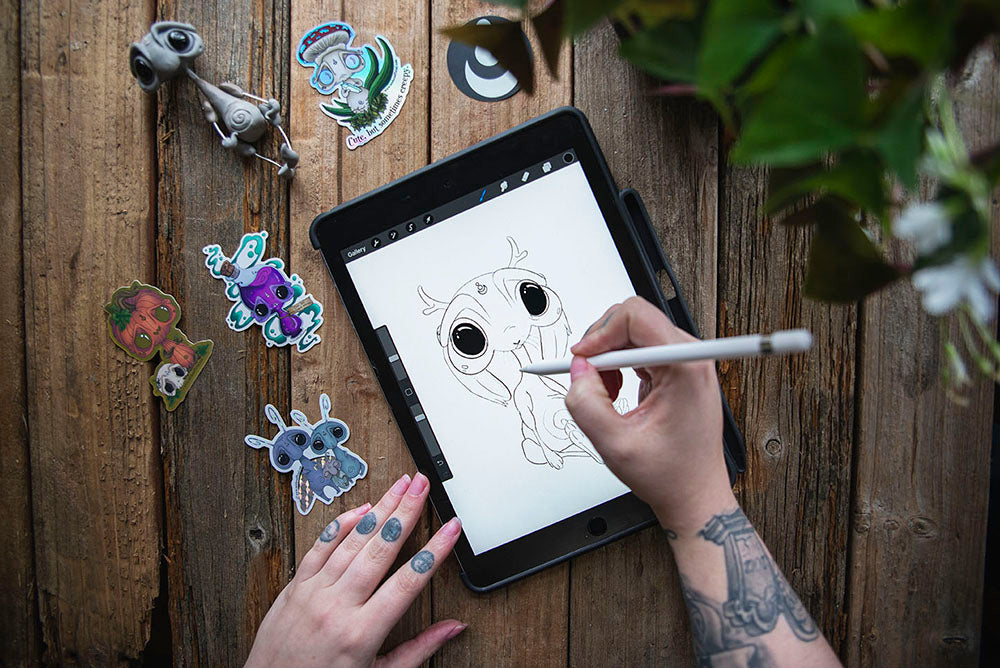Mishes Official | hands sketching jackelope on ipad, surrounded by stickers