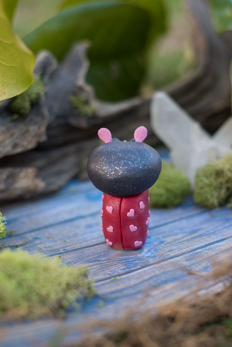 Back view of Amoura the love bug Mish - hand sculpted red and black ladybug polymer clay creature with pink hearts and rose quartz