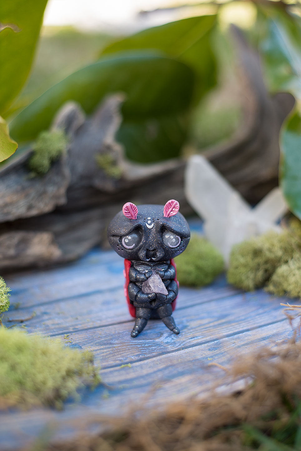 Front view of Amoura the love bug Mish - Hand sculpted red & black ladybug polymer clay creature, holding rose quartz