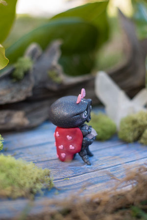 Side view of Amoura the love bug Mish - hand sculpted red and black ladybug polymer clay creature with pink hearts holding rose quartz