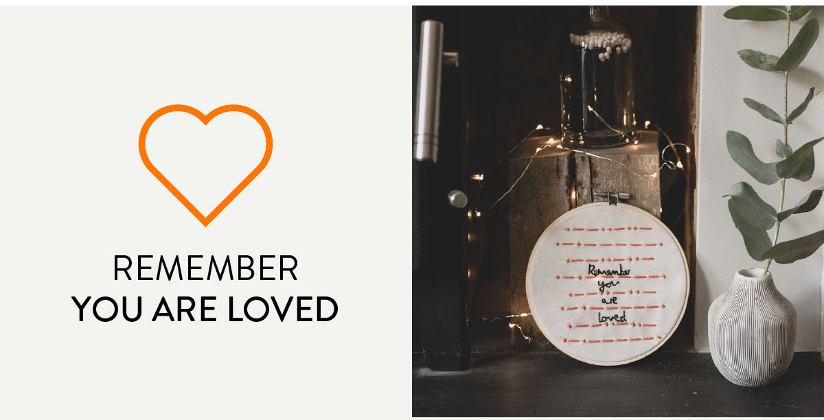 Remember you are loved. A hand embroidered hoop with the message 'remember you are loved' in english in black. The same message appears in morse code in orange threads.