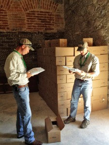 Two men reading documents beside shipping boxes.