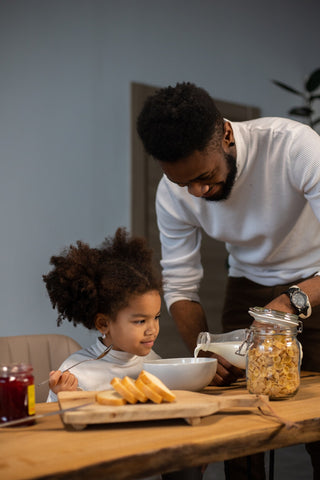 Positive black father and daughter having breakfast