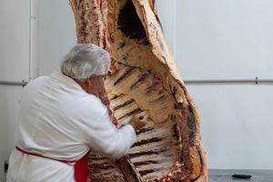 butcher preparing a grass-fed cow, aged beef from arrowhead beef
