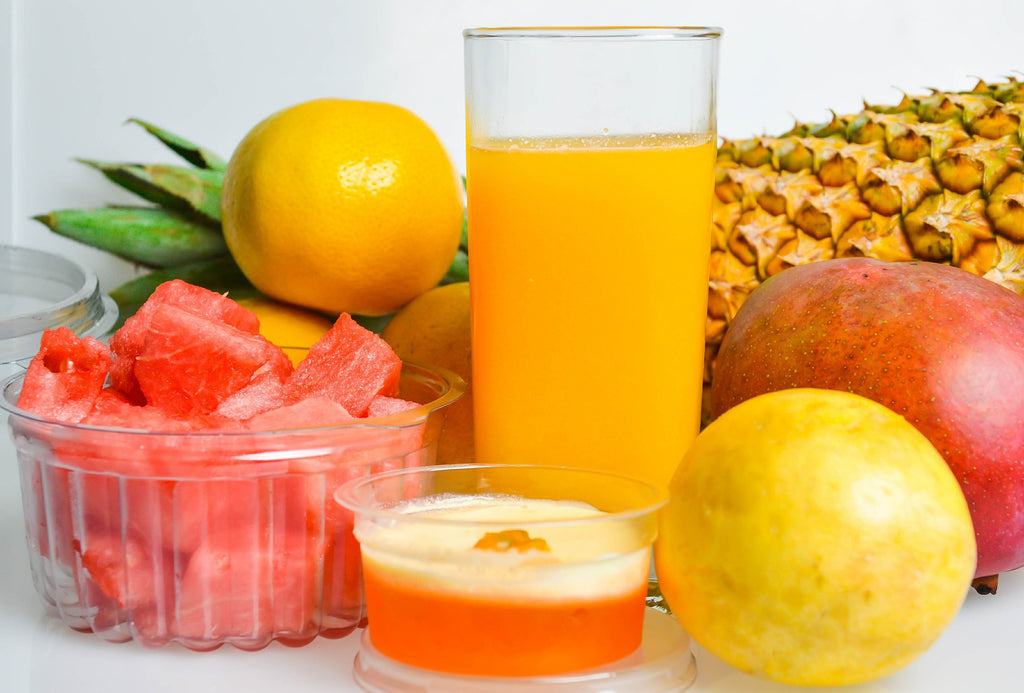 Glass of juice surrounded by fruits