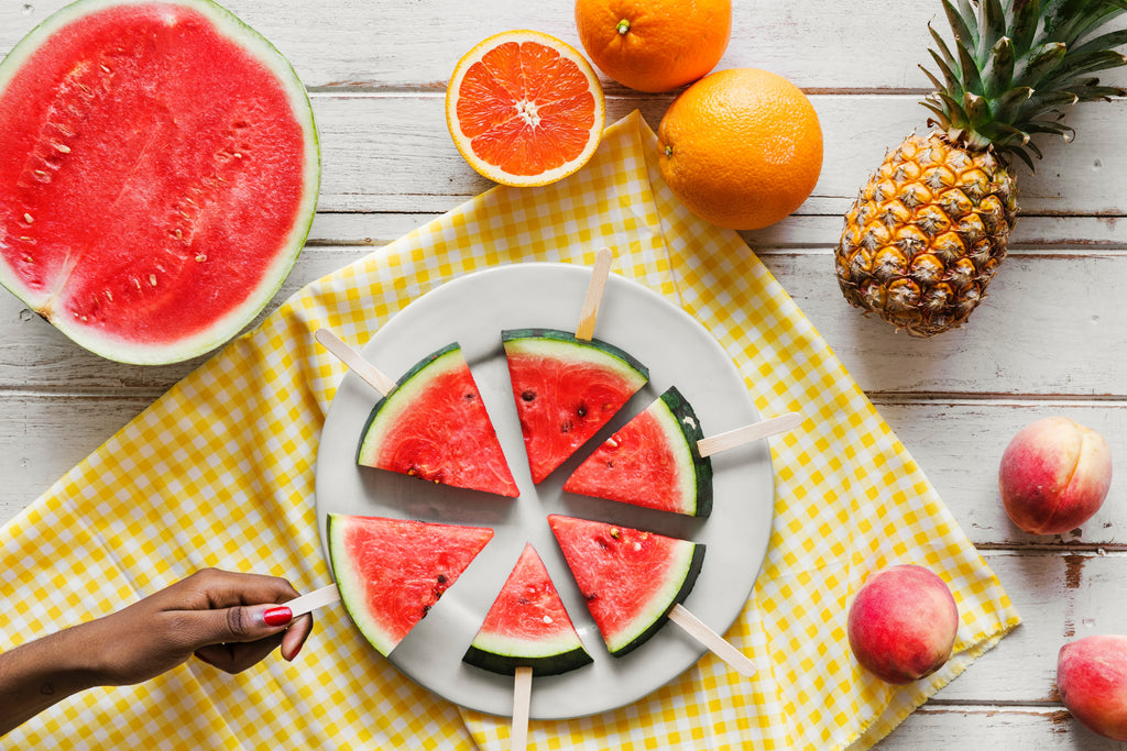 Watermelon slices on stick oranges apples and pineapple on table