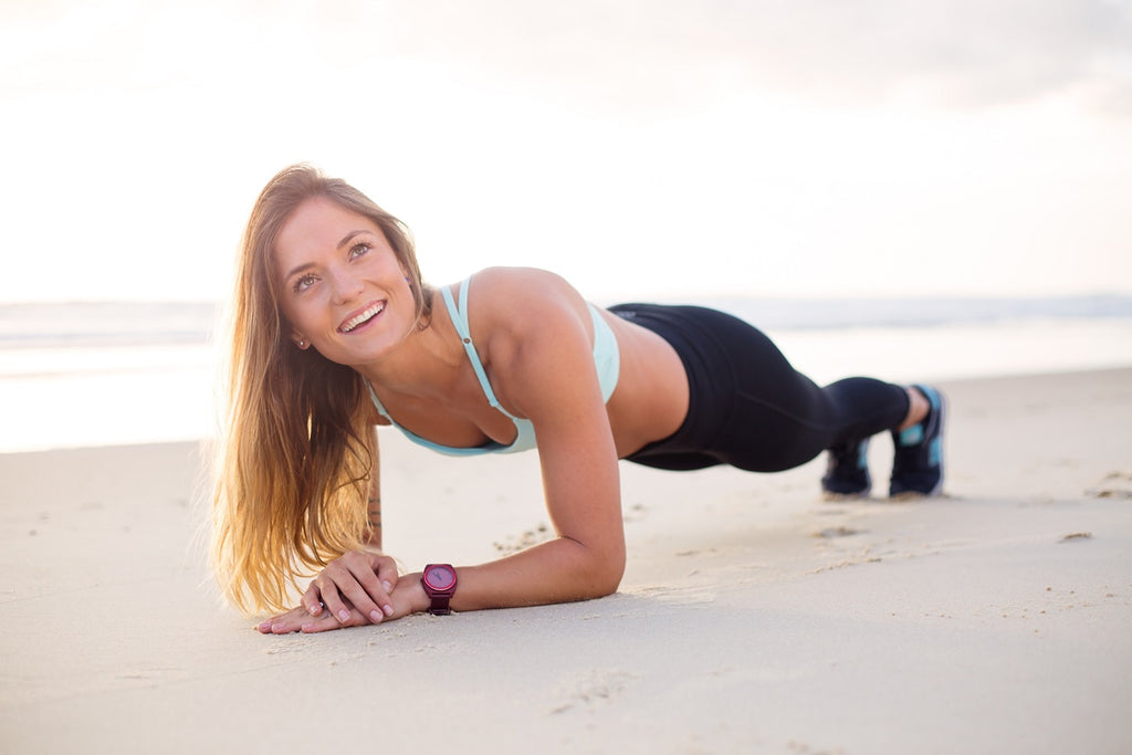 Blonde woman exercising by the beach