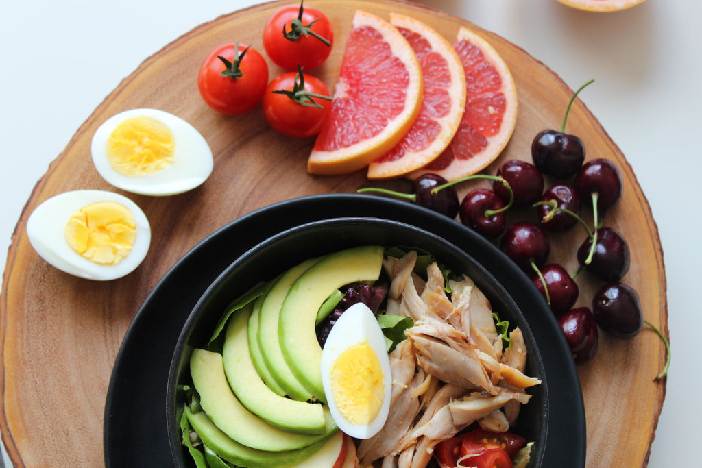 Bowl of salad and egg and grapefruit slices on chopping board