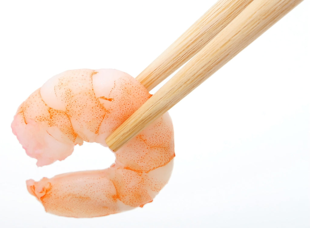 Cooked shrimp held by chopstick