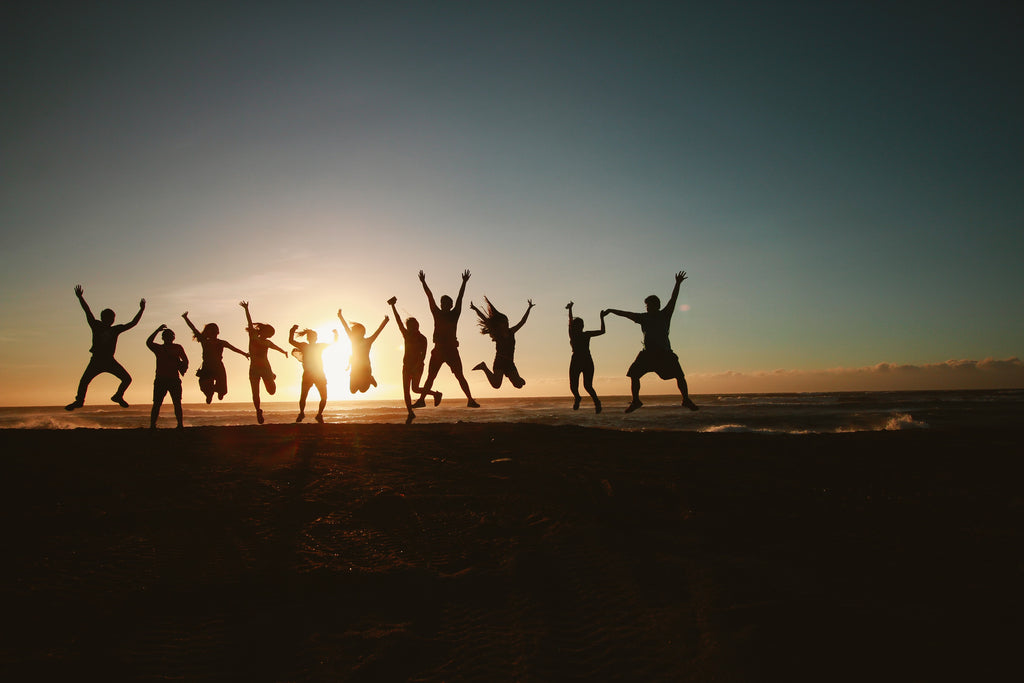 Group of people by the beach jumping and raising arms during sunset