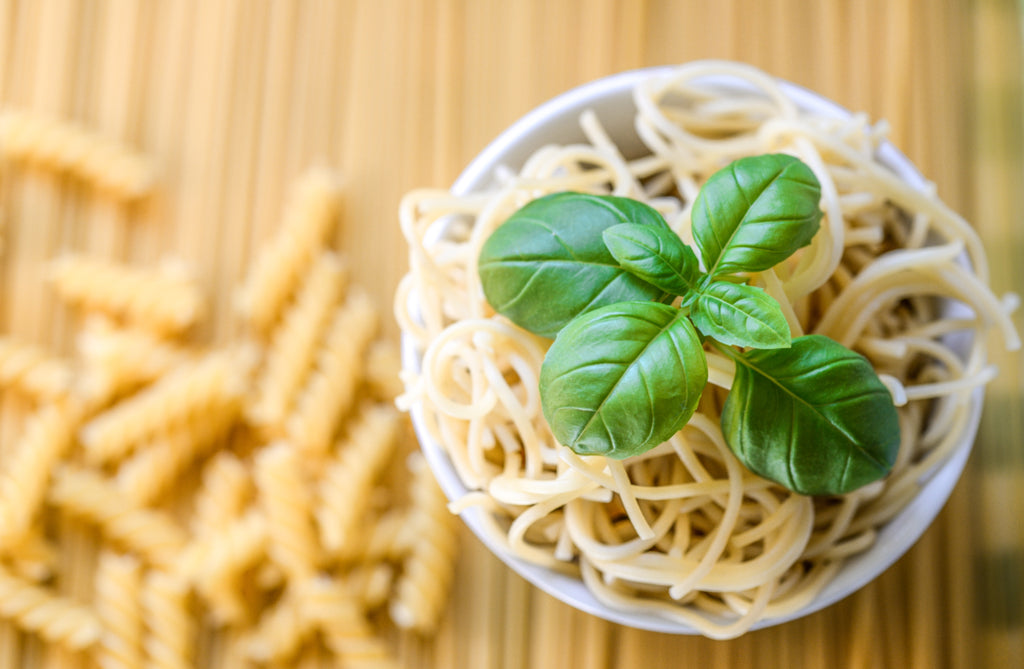 Noodles with basil on bowl