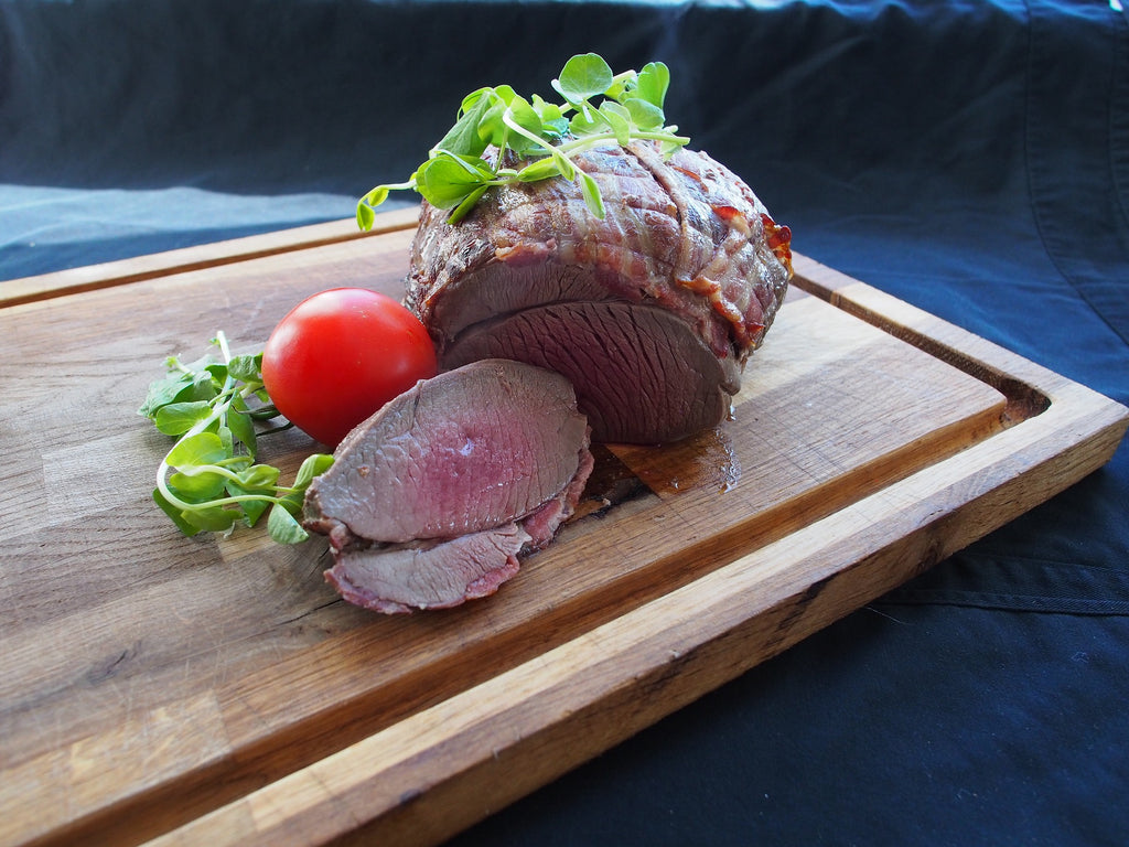 red_meat_with_tomato_and_watercress_on_chopping_board