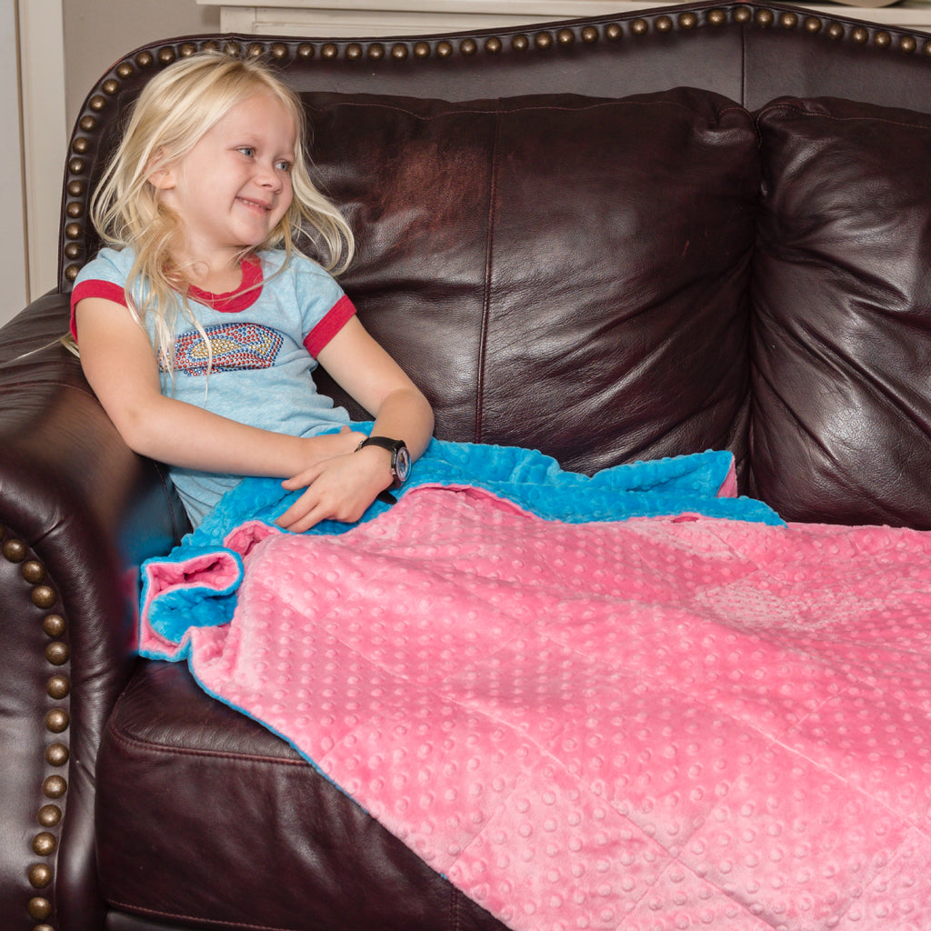 Happy little girl with a minky dot weighted blanket for kids