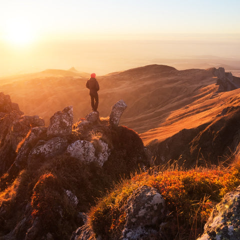 Hiker standing on mountain with sun shining