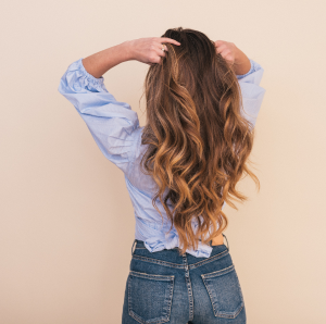 Woman running her hands through her brunette hair extensions