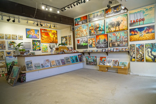 A large, open room with concrete flooring, white walls, and bright lighting. Many colorful paintings hang on the walls. More artworks are displayed along wall shelves that are about two feet above the ground.