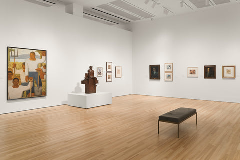 A museum gallery room with white walls and multi-colored wood flooring. There are artworks displayed along the walls and a brown sculpture in the room. There is a black bench in the middle of the room.