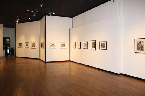An open gallery room with white walls that have black trim on the borders and dark wood floors. Several black and white artworks adorn the walls.