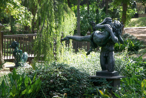 A lush, green garden with many different kinds of plants. There is a statue of a woman being held aloft by a man who is kissing her in the foreground. In the background, there is another statue of a woman and a bridge behind her.