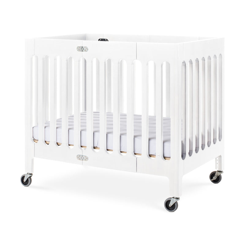 "Foundations Boutique Compact Folding Wood Crib with 3"" Foam Mattress and Oversized Casters - Matte White"