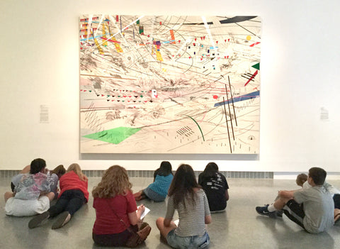Students sitting in front of a large Julie Mehretu painting, with abstract shapes and lines