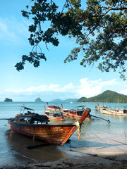 A beautiful and tranquil beach scene from Thailand with aqua water and longtail boats