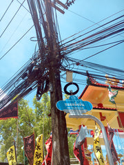 Tangled electric wires in a street scene from Phuket, Thailand with traditional buildings in the background