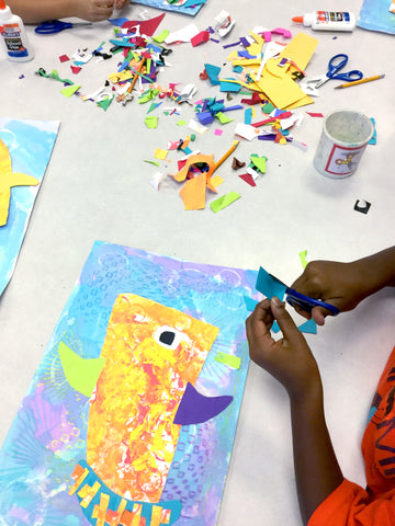 elementary student's hands working on a colorful and bright fish collage with mixed media